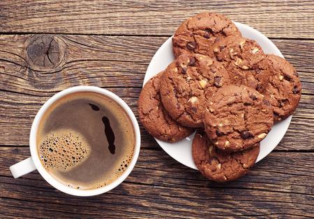 chocolate cookie: Placa con galletas de chocolate y una taza de café caliente en la mesa de madera vieja. Vista superior