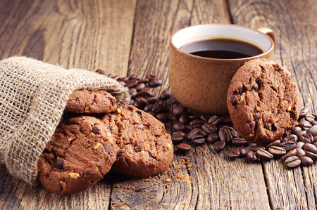 Sack with chocolate cookies and cup of hot coffee on old wooden table
