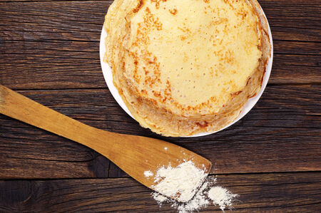wooden table top view: Tasty pancakes in a plate on vintage wooden table. Top view