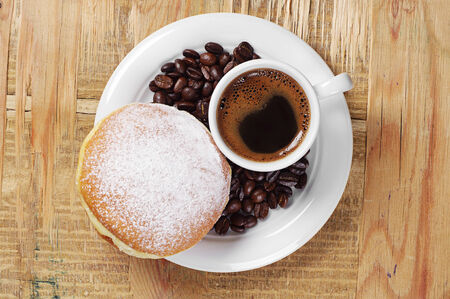 Cup of hot coffee with sweet doughnut on old wooden table. Top view photo