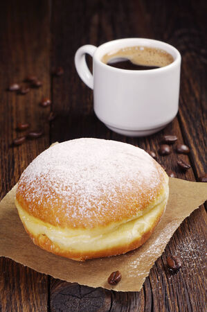 Berliner donut with cup of hot coffee on dark wooden table photo