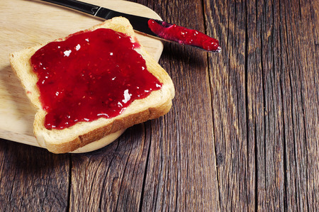 Toasted bread with jam and knife on dark wooden table
