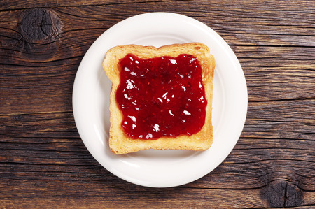 Toast with jam in white plate on dark wooden table. Top view Stok Fotoğraf