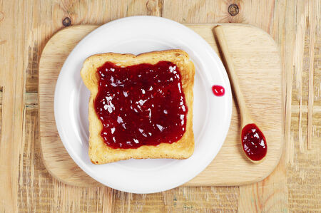 Toast with jam and wooden spoon on cutting board. Top view photo
