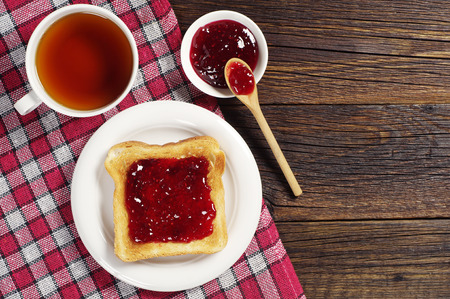 Toast with jam and cup of tea on wooden table covert tablecloth. Top view photo