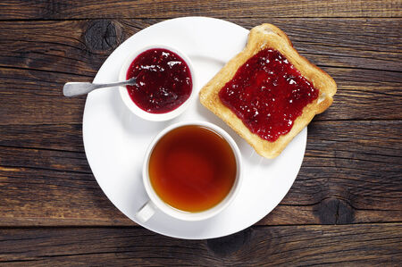 Toast with jam and cup of tea on dark wooden table. Top view photo