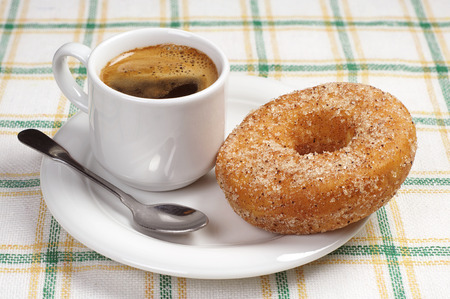covert: Breakfast with donut and cup of hot coffee on a table covert tablecloth Stock Photo