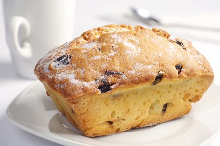 Sweet cupcake with raisins on white plate closeup photo