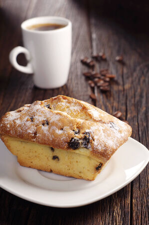 Sweet cupcake with raisins and cup of hot coffee on dark wooden table photo