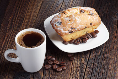 Black coffee and cupcake with raisins on dark wooden table photo
