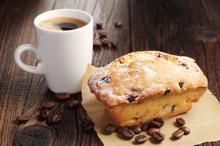 Cupcake with raisins and cup of hot coffee on dark wooden table photo