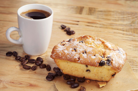 Sweet cupcake with raisins and coffee cup on old wooden table photo