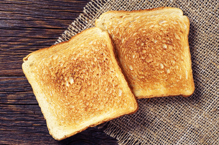 Two toast bread on wooden background closeup. Top view