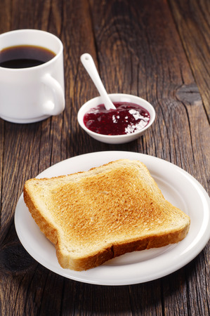 Toast with raspberry jam and cup of coffee on dark wooden table
