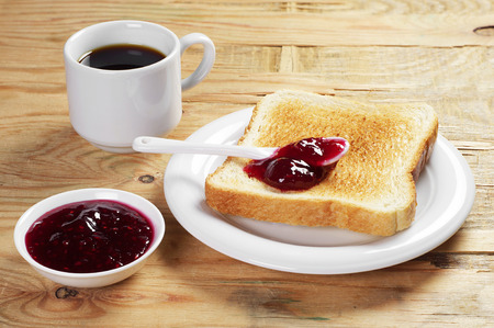 Toast with raspberry jam and cup of hot coffee on old wooden table
