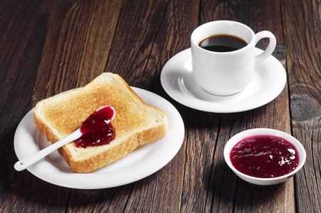 Toast with jam and cup of black coffee on dark wooden table