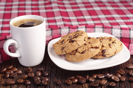 covert: Chocolate cookies in plate and cup of hot coffee on wooden table covert tablecloth