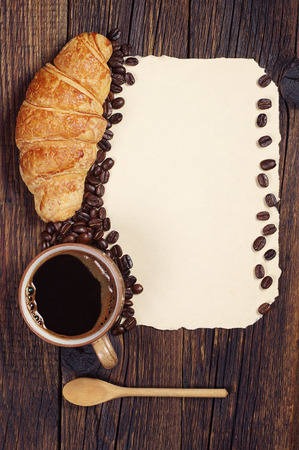 Cup of hot coffee, croissant and blank sheet of old paper as a background, top view
