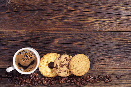Various sweet cookies and cup of hot coffee on dark wooden table, top view photo