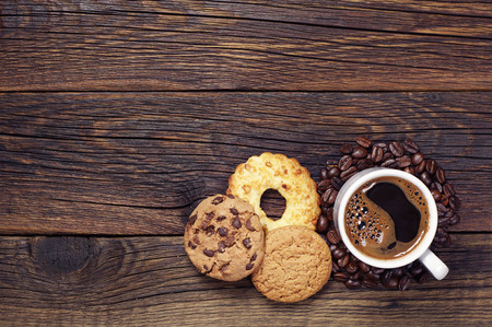 Cup of hot coffee and various sweet cookies on dark wooden table, top view