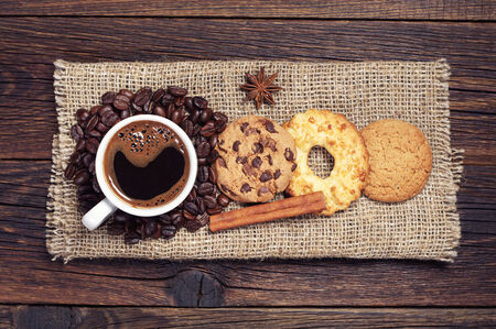 Cup of hot coffee and various sweet cookies on dark wooden table with burlap, top view photo