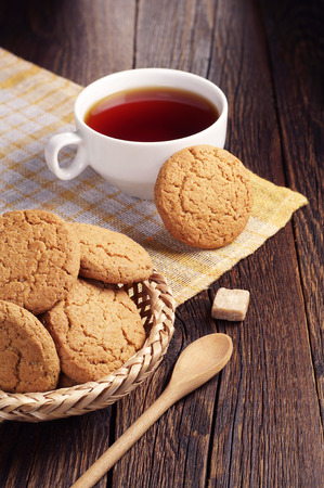 oatmeal cookie: Oatmeal cookie and cup of tea on dark wooden table covert yellow tablecloth