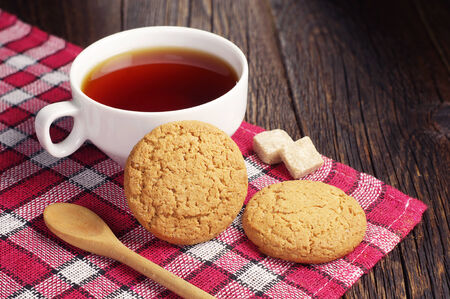 covert: Tea cup with oatmeal cookie on dark wooden table covert red tablecloth Stock Photo
