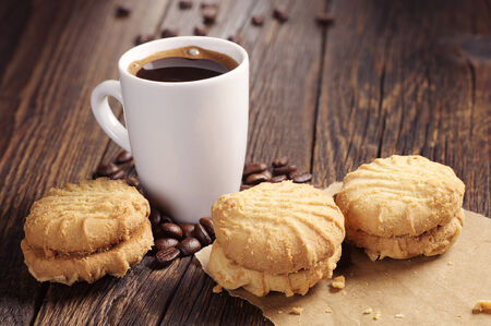 Cup of hot cookies and sweet cookies on dark wooden table