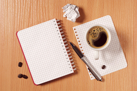 Notebook, crumpled paper, pen and coffee cup on desk, top view photo
