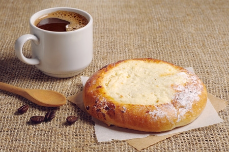 covert: Pie with cottage cheese and cup of hot coffee on table covert burlap