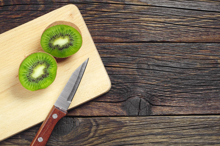 Fresh sliced kiwi fruit and knife on wooden board, top view Stock Photo