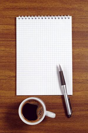 papel de notas: Inaugurado el bloc de notas, bol�grafo y una taza de caf� en el escritorio, vista desde arriba