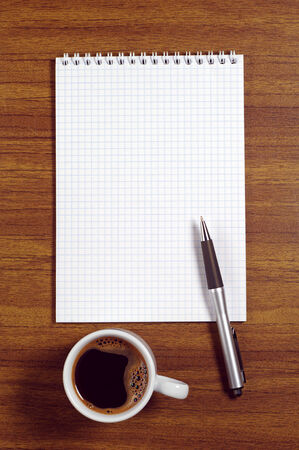 note paper: Opened notepad, pen and coffee cup on desk, top view Stock Photo