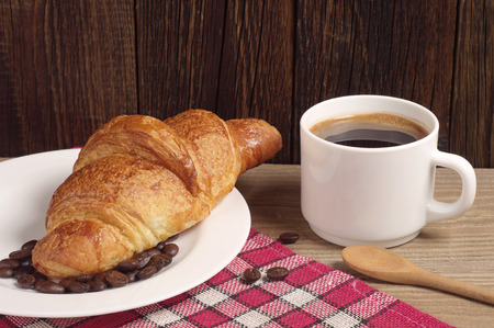 covert: Breakfast with croissant and coffee on wooden table covert red tablecloth