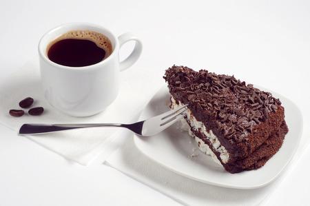 rebanada de pastel: Pedazo de pastel de chocolate y una taza de café caliente sobre fondo blanco