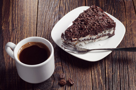 Cup of hot coffee and chocolate cake on dark wooden table