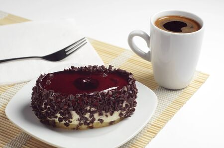 coffee jelly: Chocolate cake with cherry jelly and cup of hot coffee on bamboo napkin Stock Photo