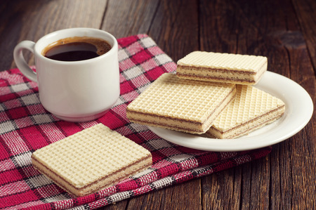 covert: Wafers with chocolate and cup of hot coffee on wooden table, covert red tablecloth