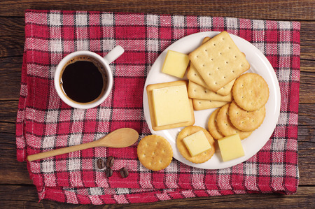 Cracker cookies with cheese and coffee cup on red tablecloth, top view