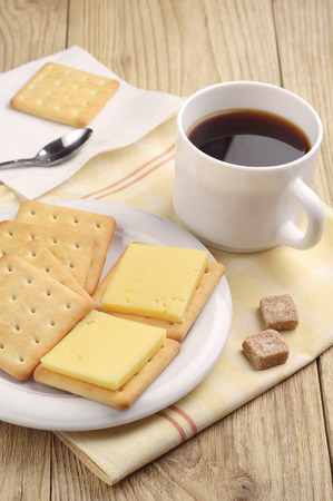 Cracker cookies with cheese and cup of black coffee on wooden table