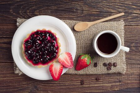 breakfast plate: Cup of coffee, cake with black currants and strawberry on wooden table, top view