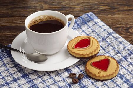 Cup of coffee and cookies with jam on blue tablecloth photo