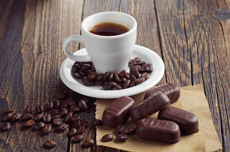 dark chocolate: Cup of hot coffee with chocolates on dark wooden table