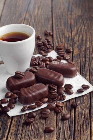 cafe bombon: Taza de caf� y dulces de chocolate en la mesa de madera vieja