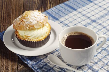 covert: Tasty cake with coffee cup on table covert blue tablecloth