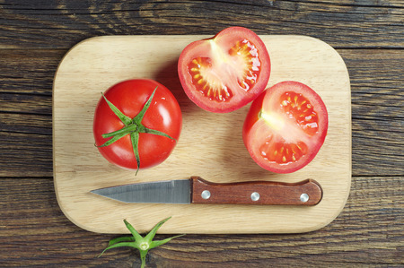 Red tomato slices and knife on cutting board, top view Stock Photo