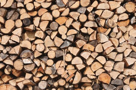 Background of dry chopped firewood stacked up in a pile
