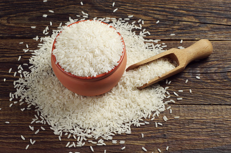 bowl with rice: Bowl full of white rice and scoop on dark wooden table