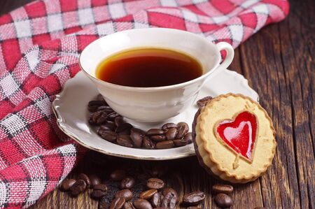 covert: Cup of coffee with cookie on rustic table covert red tablecloth Stock Photo