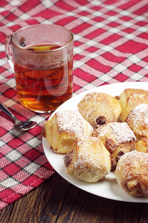 covert: Cookies with raisins in plate and tea cup on table covert red tablecloth